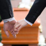Couple holding hands in funeral