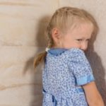 Little girl standing in corner