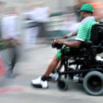Man using electric wheelchair on sidwalk