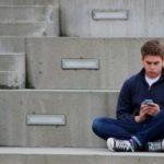 Young teenage boy texting