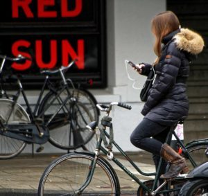 Young woman texting and biking