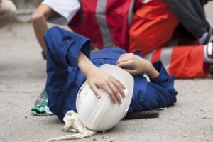 Injured construction worker laying on ground