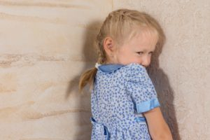 Child standing in the corner