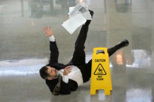 Business man slips on wet floor