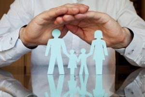 Man placing hands over paper family