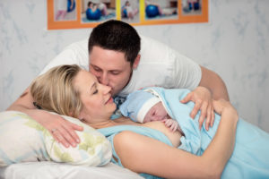 New parents holding newborn baby