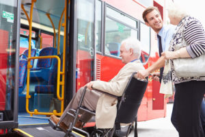 Man helping senior couple board bus