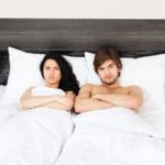Upset young couple in bed