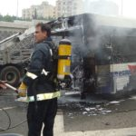 Firemen extinguishing fire on bus