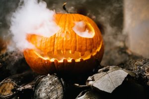 one jack-o-lantern on wood with smoke rising