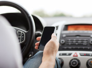 man driving while using phone