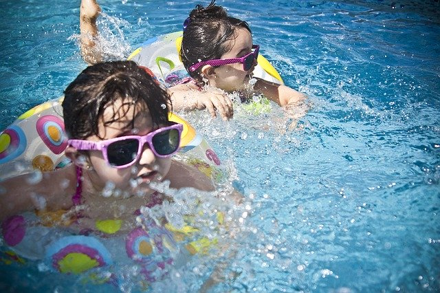Girls wearing sunglasses are swimming in the pool