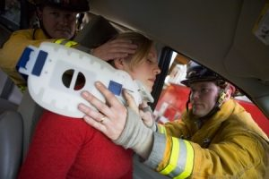 Firefighters are putting a medical neck brace to a woman