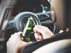 Man opening a bottle of beer while driving