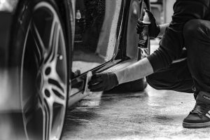Auto worker is cleaning a car