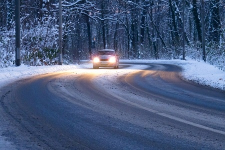 Car with high beams driving on snowy road