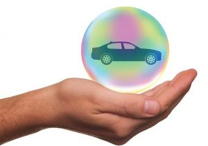 Hand holding a bubble with a car model in it, car insurance