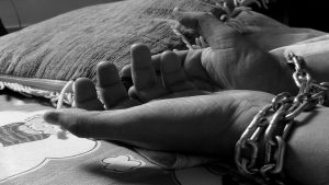 Hands with iron chain, human trafficking