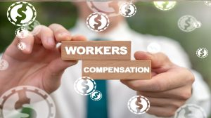 Businessman holding two blocks with words workers compensation