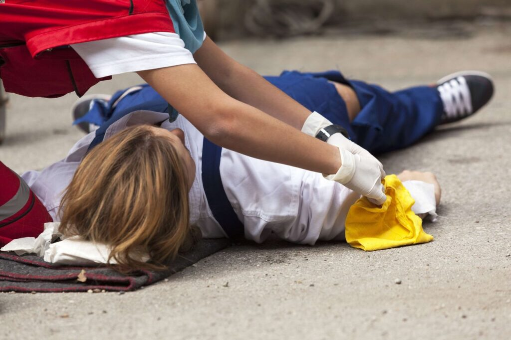 An injured worker lying down on ground