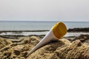 sunscreen product in sand, sun cream